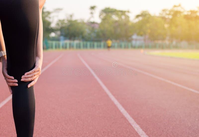 De vrouw houdt op de knie, Atletenpijn in de knie stock fotografie