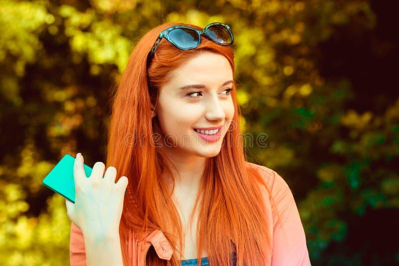 De vrouw houdt de telefoon in rechts haar en kijkt glimlachend aan de linkerzijde, op groen stock foto