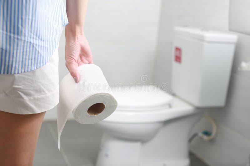 De vrouw houdt toiletpapierbroodje voor toiletkom stock foto's