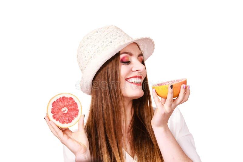 De vrouw houdt twee halfs van grapefruitcitrusvruchten in handen stock afbeeldingen