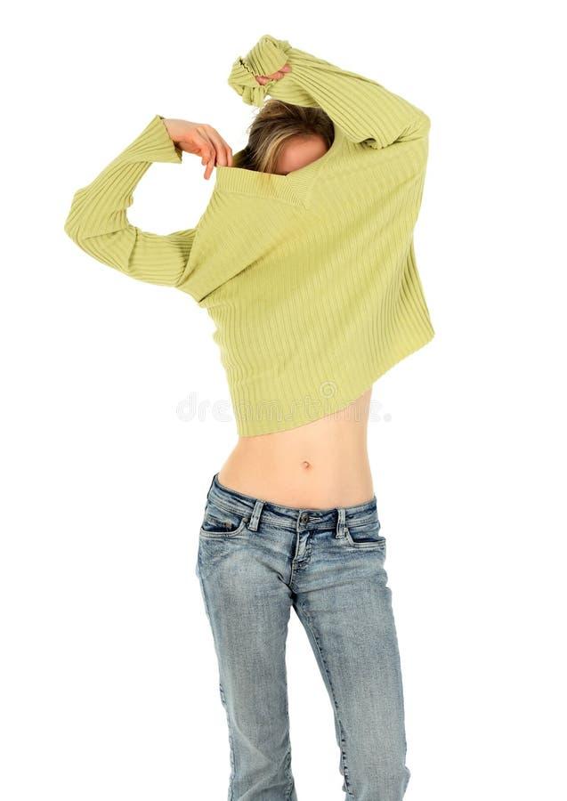 De vrouw in jeans stijgt een groene sweater op stock fotografie