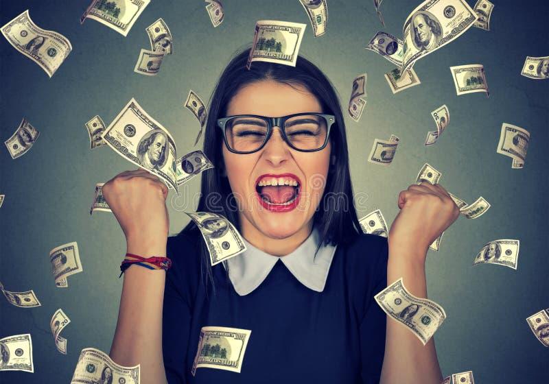 De vrouw jubelt pompende extatische vuisten viert succes onder geldregen stock afbeeldingen