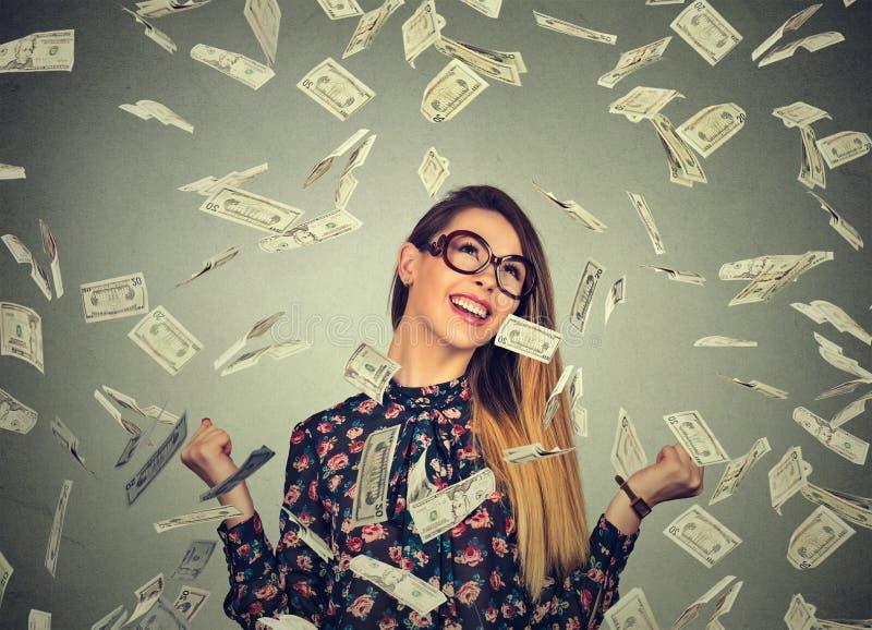 De vrouw jubelt pompende extatische vuisten viert succes onder geldregen die onderaan de bankbiljetten van dollarrekeningen valle royalty-vrije stock foto's