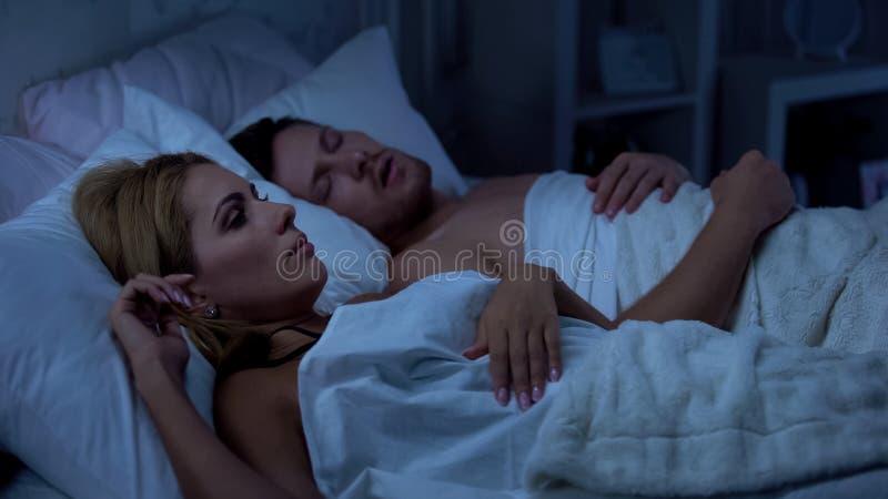 De vrouw kan niet slapen, echtgenoot het snurken met open mond, gezondheidsproblemen, dysfunctie stock fotografie