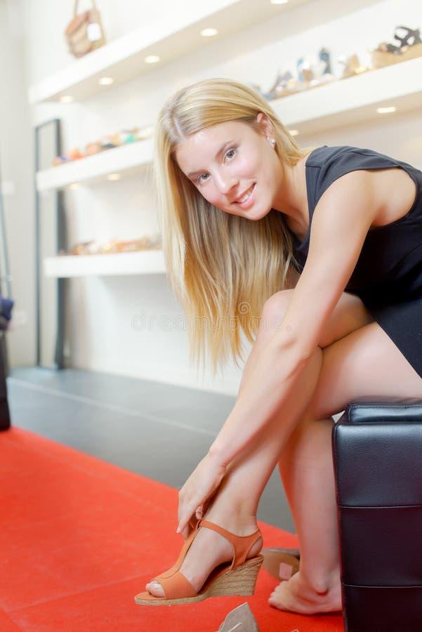 De vrouw kan zich ` t tegen het proberen op schoenen verzetten royalty-vrije stock foto's