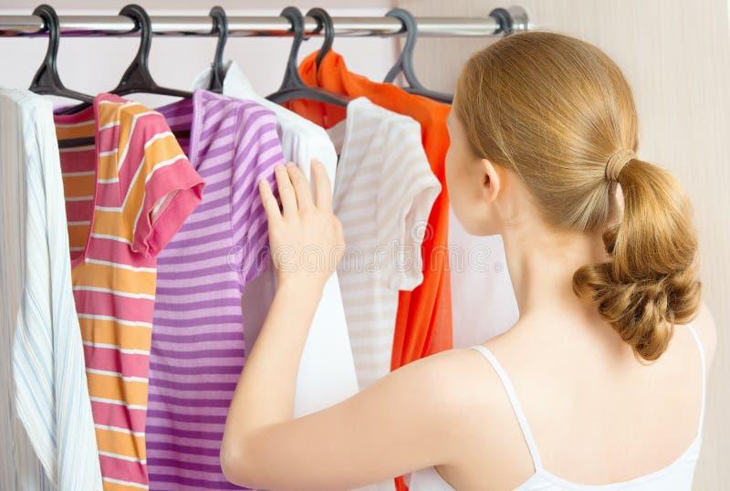 De vrouw kiest kleren thuis in de garderobekast royalty-vrije stock afbeelding