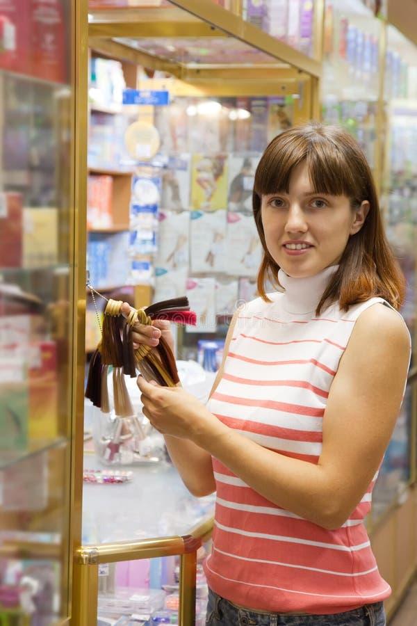 De vrouw kiest kleur van haar-kleurstof royalty-vrije stock afbeelding