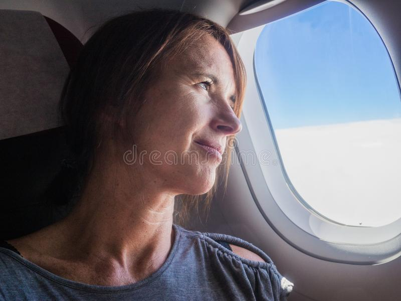 De vrouw kijkt door een venster in de vliegtuigen stock foto's