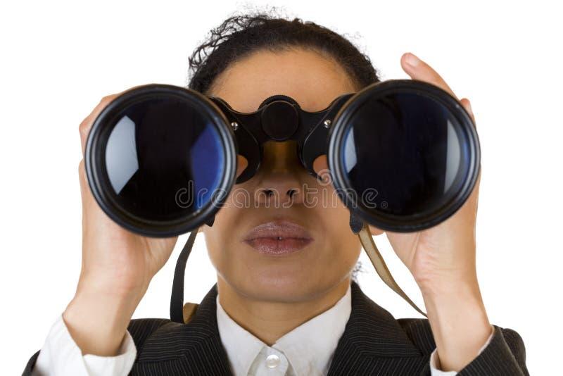 De vrouw kijkt door verrekijkersonderzoek naar zaken stock afbeeldingen