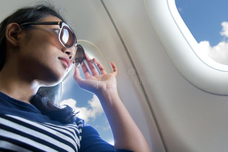 De vrouw kijkt uit het venster van een vliegend vliegtuig stock foto's