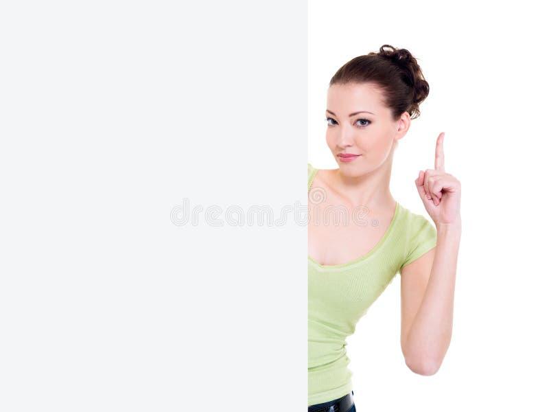 De vrouw kijkt van aanplakbord met lift omhoog wijsvinger stock foto's