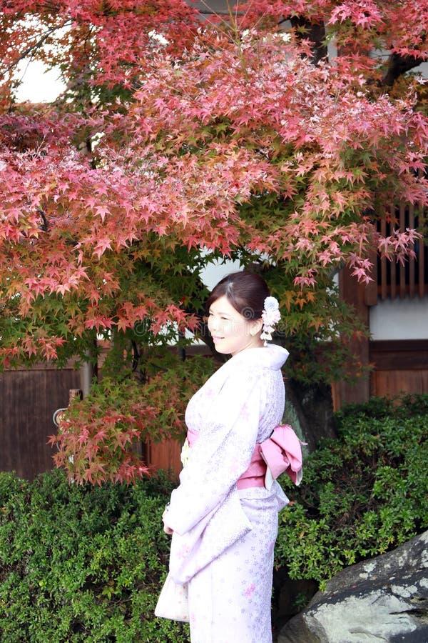 De vrouw in Kimonokleding en de roze sjerp die zich met rode bladeren als achtergrond in de herfst bevindt tuinieren bij Kiyomizu stock fotografie