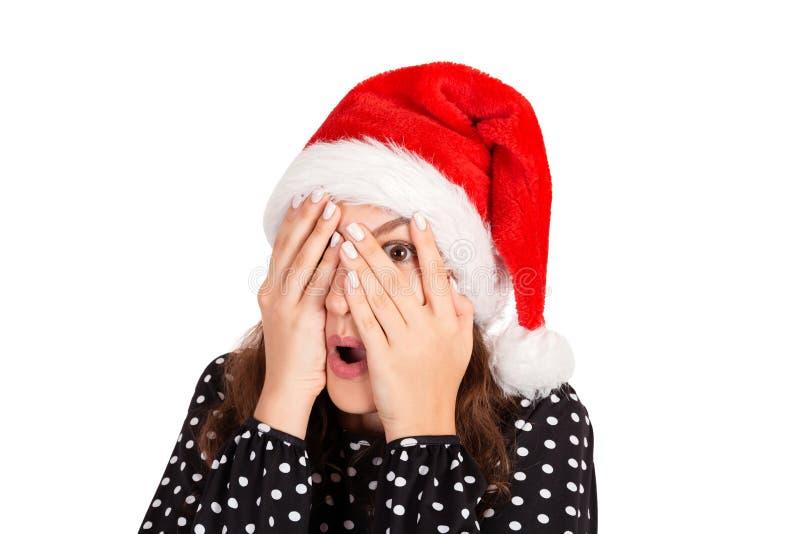 De vrouw in kledingsgevoel deed schrikken maar nieuwsgierig met één oog glurend door vingers emotioneel meisje in Kerstmishoed va royalty-vrije stock foto's