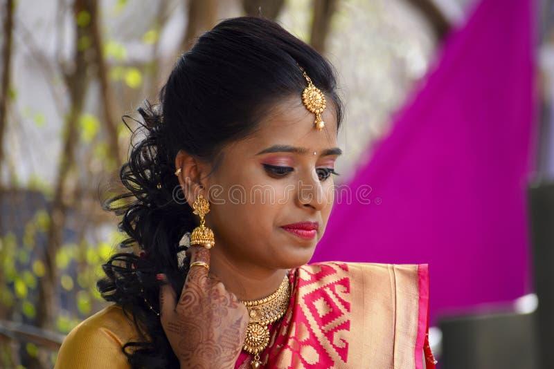 De vrouw kleedde zich in Indische kledij en juwelen neer kijkend, Pune stock fotografie