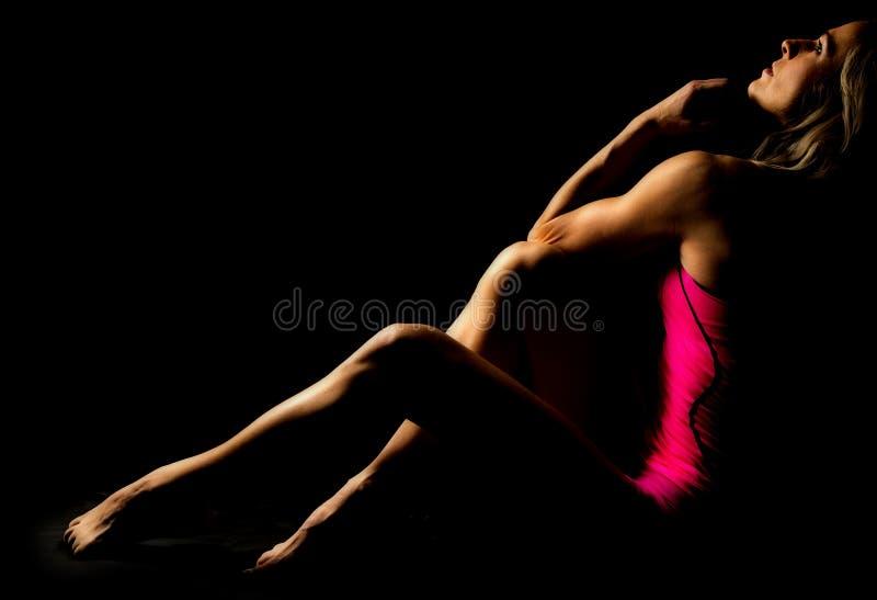 De vrouw kleedde zich in roze zitting kijkend omhoog hoogtepunt stock foto