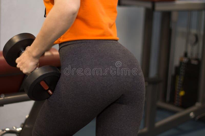 De vrouw kleedde zich in sportslijtage uitwerkend in een gymnastiek opheffend zwaar w stock afbeeldingen