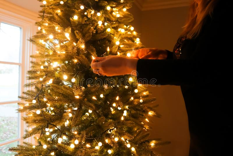 De vrouw kleedde zich in zwarte het verfraaien Kerstmisboom met lichten royalty-vrije stock foto's