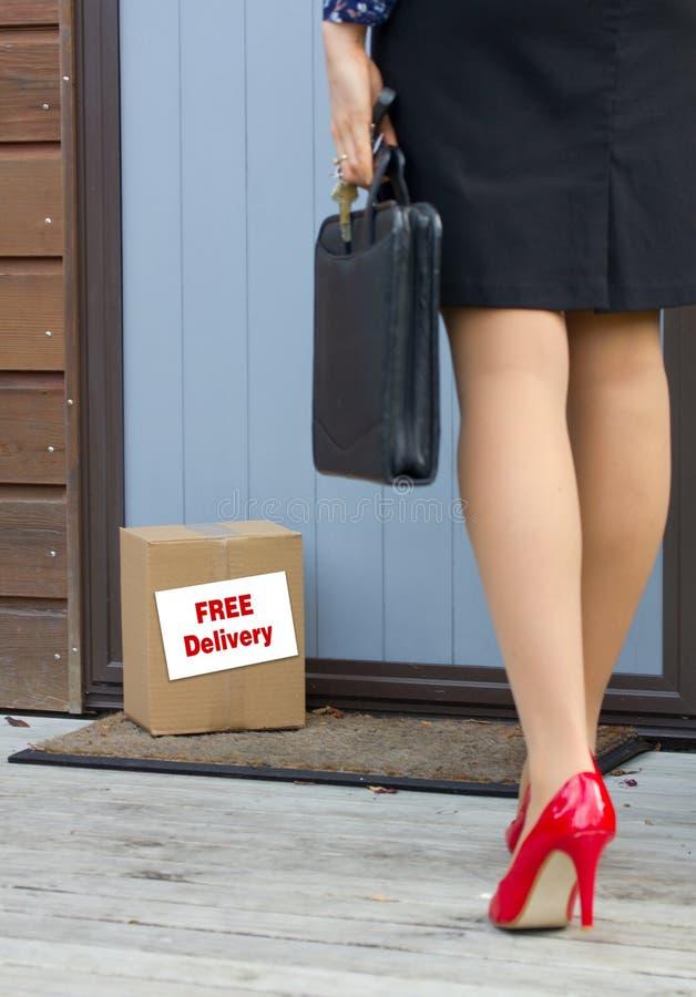 De vrouw komt naar huis na het werk aan aan vrij leveringspakket bij deur royalty-vrije stock foto