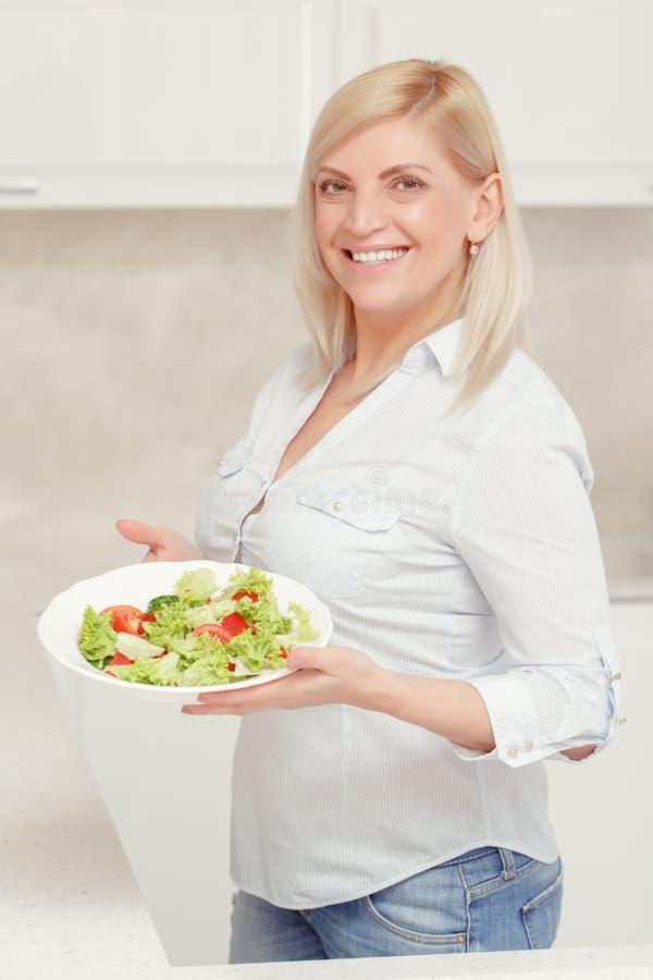 De vrouw kookt salade in de keuken stock afbeeldingen