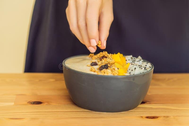 De vrouw kookt smoothie kommen met mango, banaan, granola, geraspte kokosnoot, draakfruit, chiazaden en munt die op houten worden stock fotografie
