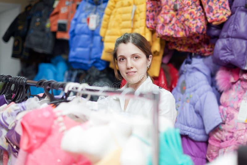 De vrouw koopt kleren voor weinig dochter royalty-vrije stock fotografie