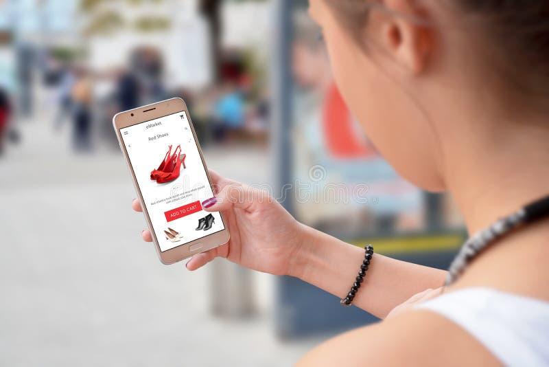 De vrouw koopt online met het winkelen app op slimme telefoon stock foto's