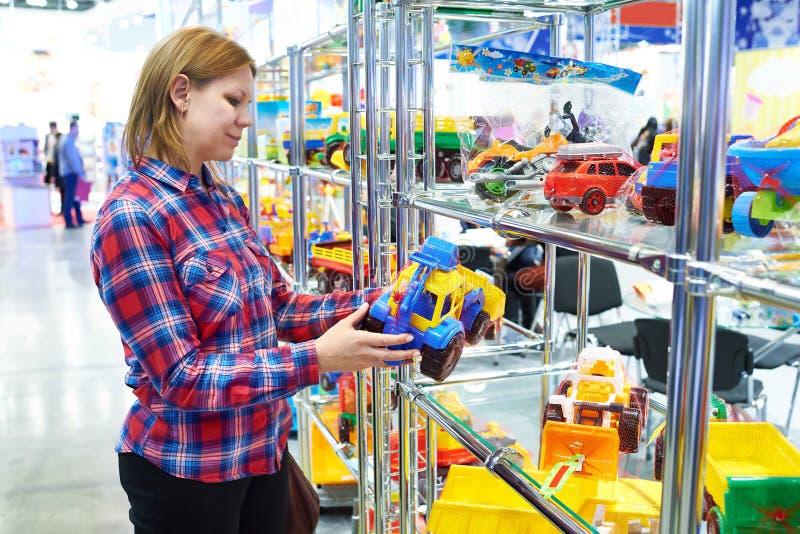 De vrouw koopt stuk speelgoed auto in kinderenopslag royalty-vrije stock fotografie
