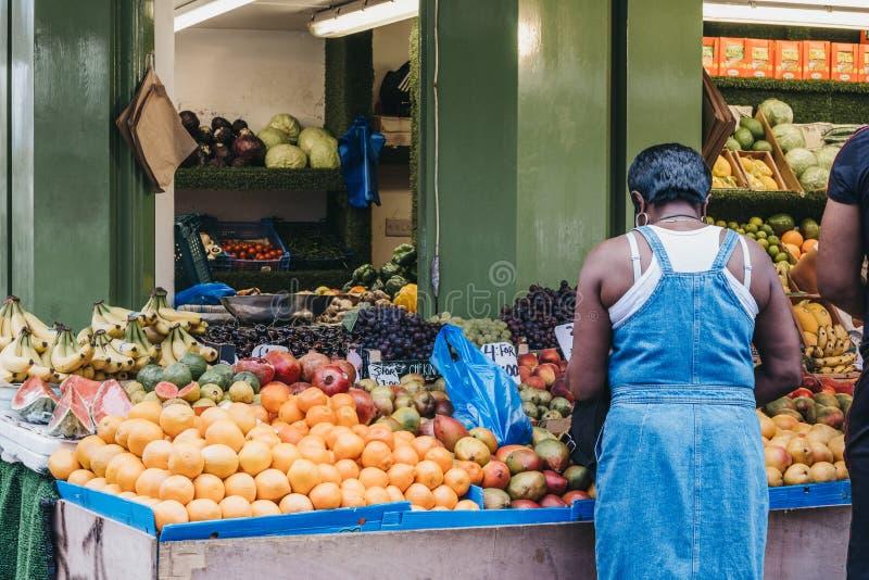 De vrouw koopt verse vruchten en groenten van Brixton Market, Zuid-Londen, het UK stock fotografie