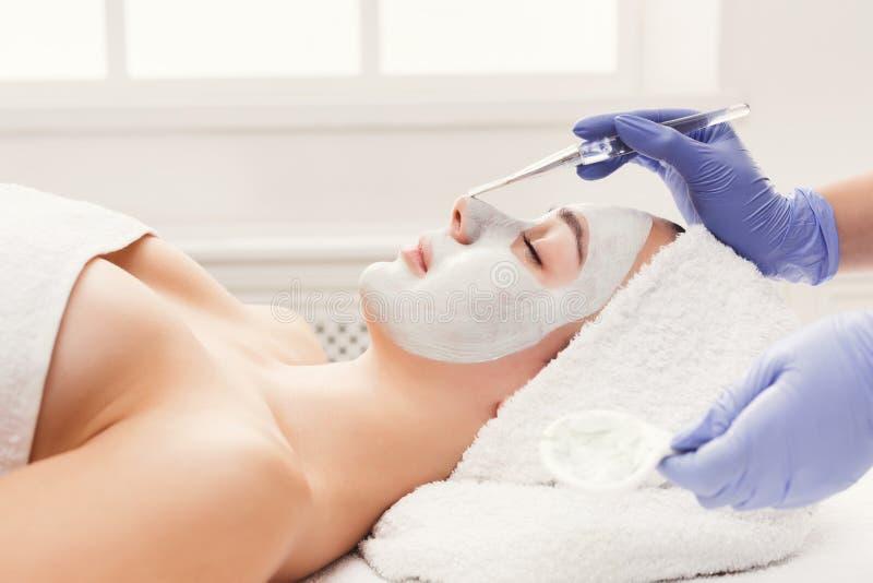 De vrouw krijgt gezichtsmasker door schoonheidsspecialist bij kuuroord royalty-vrije stock foto's