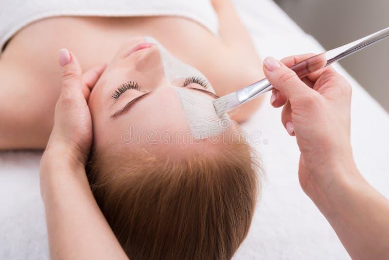 De vrouw krijgt gezichtsmasker door schoonheidsspecialist bij kuuroord royalty-vrije stock fotografie