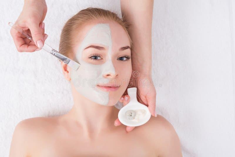 De vrouw krijgt gezichtsmasker door schoonheidsspecialist bij kuuroord stock afbeeldingen