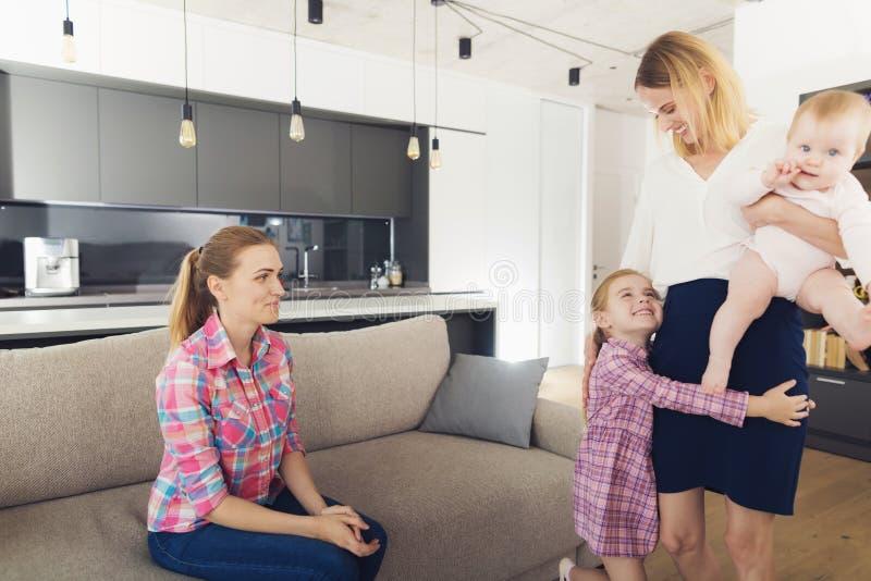 De vrouw kwam naar huis en koestert haar kinderen Een babysitter zit naast hen royalty-vrije stock foto