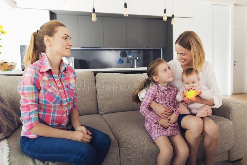 De vrouw kwam naar huis en koestert haar kinderen Een babysitter zit naast hen stock foto's