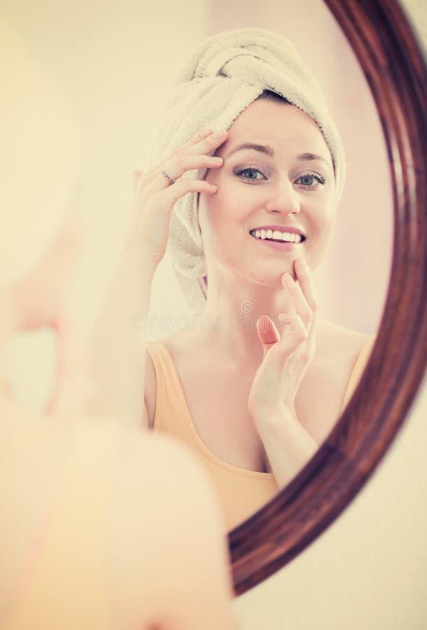 De vrouw kwam uit de douche en status naast de spiegel royalty-vrije stock afbeeldingen