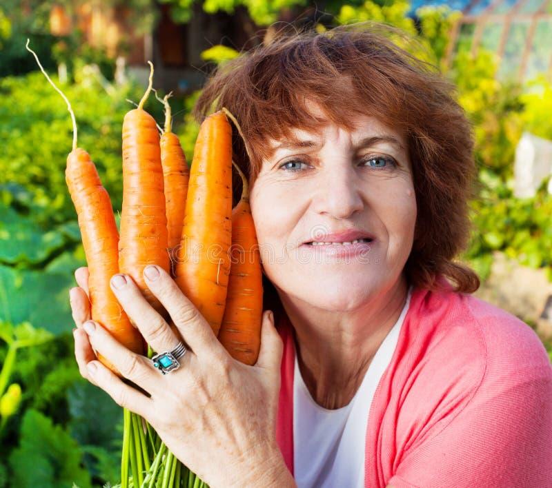 De vrouw kweekt oogst in de tuin royalty-vrije stock afbeeldingen