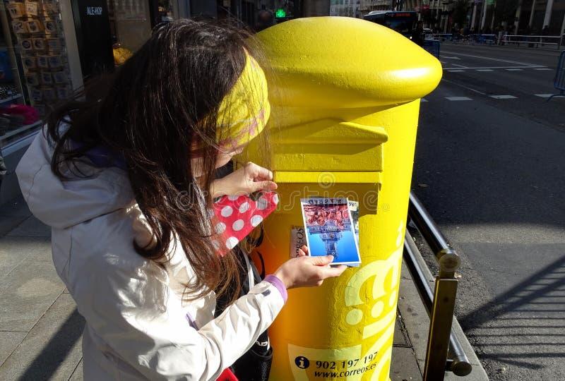 De vrouw laat vallen prentbriefkaar in straatpostbox in Madrid, Spanje stock foto