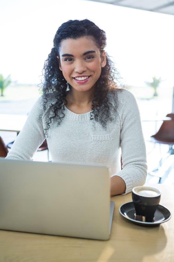 De vrouw laptop met behulp van en een koffiekop die op de lijst in de koffie winkelen stock foto