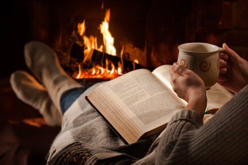 De vrouw leest boek dichtbij open haard royalty-vrije stock afbeelding