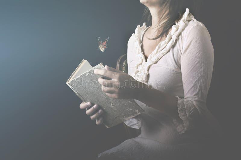 De vrouw leest een boek waar de vlinders als stroom van dromen en gedachten uitgaan stock afbeeldingen