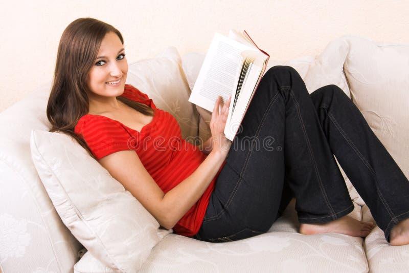 De vrouw leest op een zitkamer stock foto's