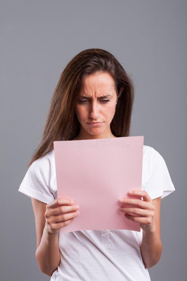 De vrouw leest slecht nieuws op een roze blad stock afbeeldingen