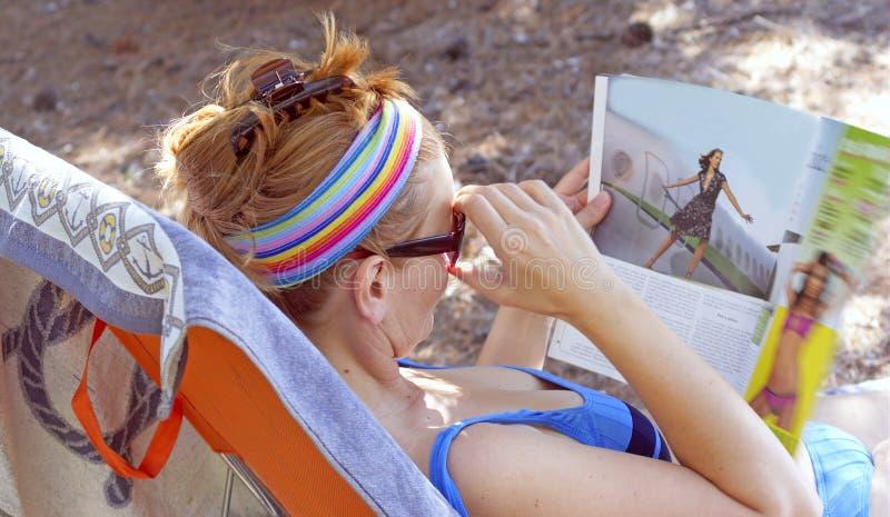 De vrouw leest tijdschrift royalty-vrije stock fotografie