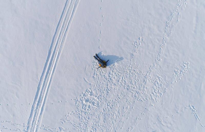 De vrouw legt op buizenstelsel in de sneeuw Luchtfoto royalty-vrije stock afbeeldingen
