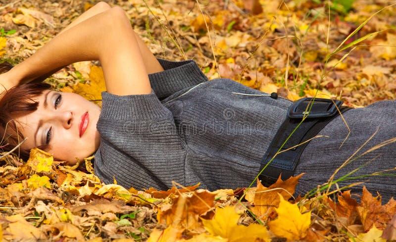 De vrouw ligt in bladeren royalty-vrije stock foto's