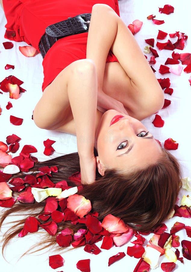 De vrouw ligt in bloemblaadjes van rozen stock afbeeldingen