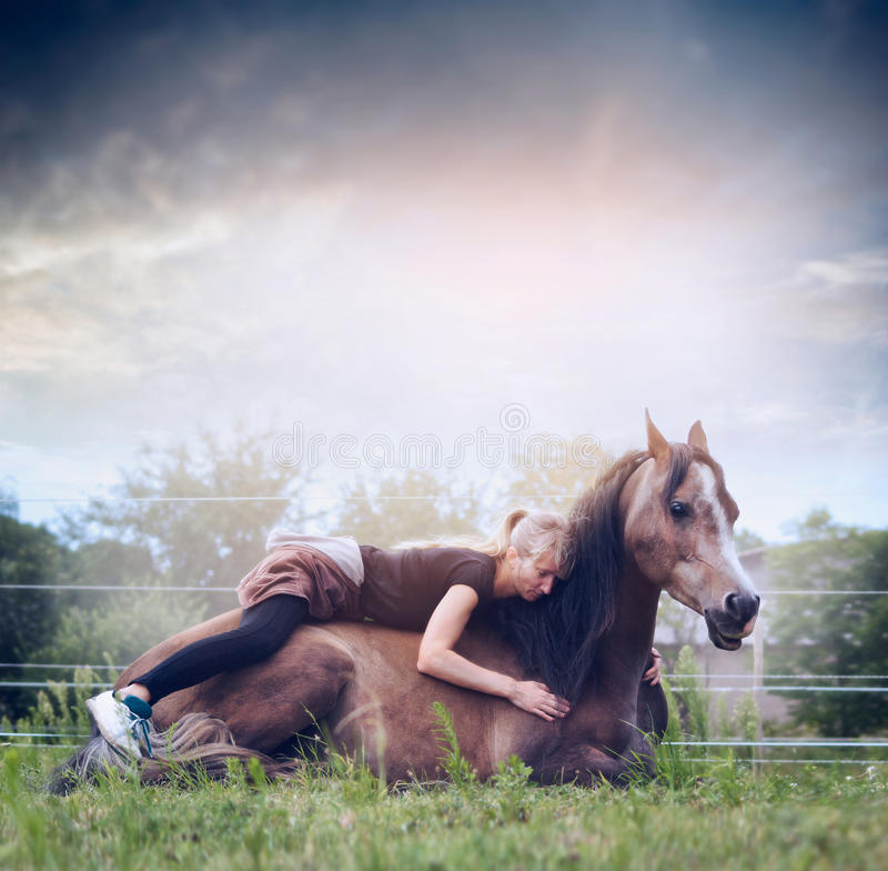 De vrouw ligt en omhelst een het rusten paard op aardachtergrond met hemel royalty-vrije stock afbeelding
