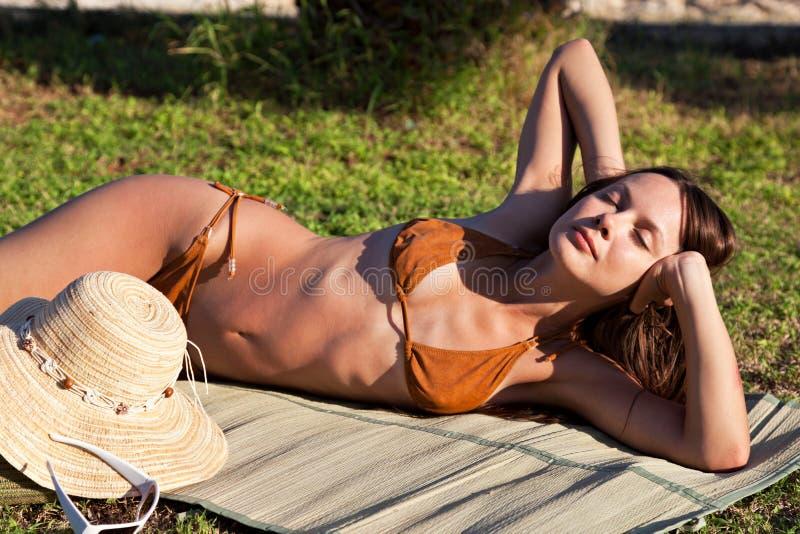 De vrouw ligt op groen gras dichtbij het overzees royalty-vrije stock foto