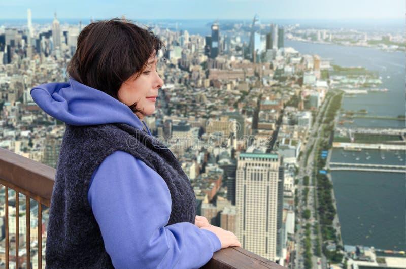 De vrouw lijdt aan acrofobie op het het bekijken platform boven een grote stad stock afbeelding