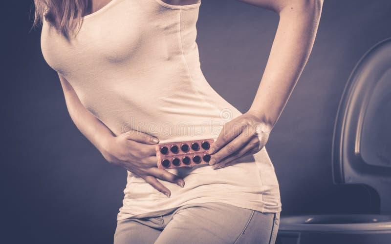 De vrouw lijdt aan buikpijn houdt pillen in toilet stock foto
