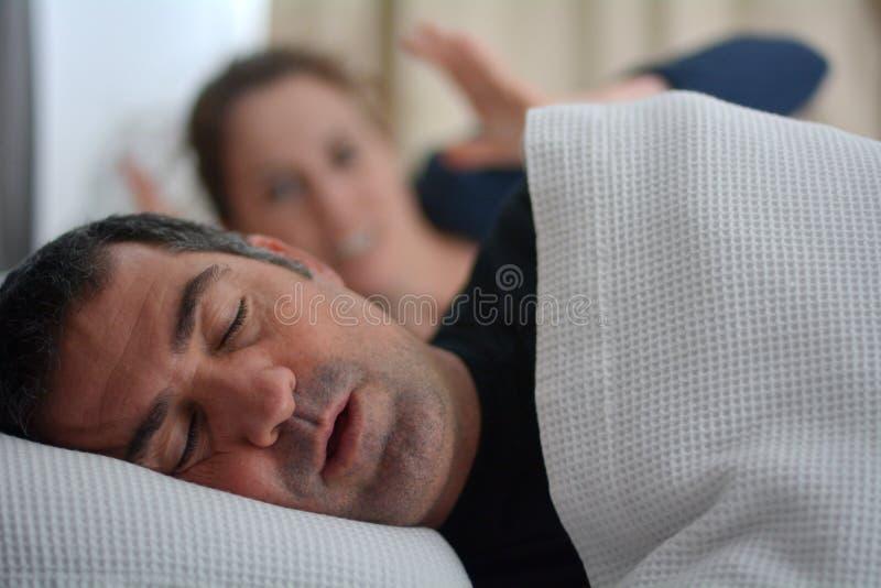De vrouw lijdt aan haar mannelijke partner snurkend in bed stock afbeelding